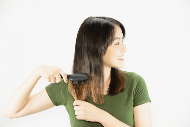 Молодая красивая дама счастлива с помощью расчески, чтобы выпрямить волосы
