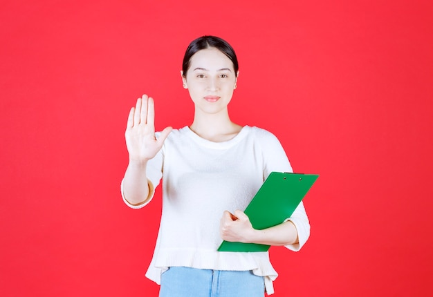 Young beautiful lady holding clipboard and gesturing stop