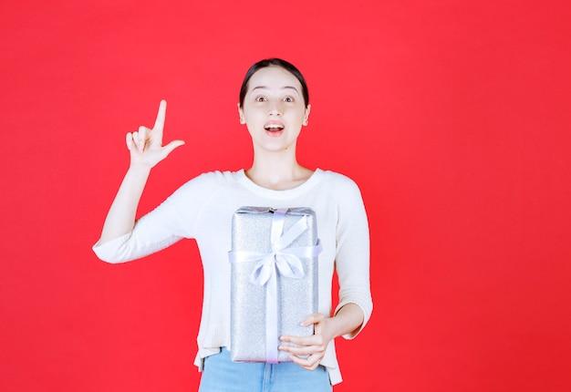 Giovane bella signora che tiene una confezione regalo sul dito puntato in alto