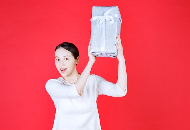 Young beautiful lady holding gift box top of her head