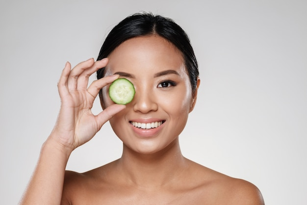 Young beautiful lady holding slices of cucumber