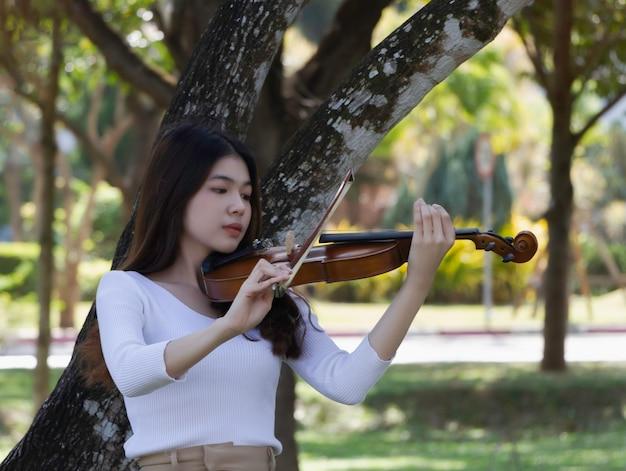 バイオリンを手に持つ若い美しい女性、アコースティック楽器の演奏方法を示す