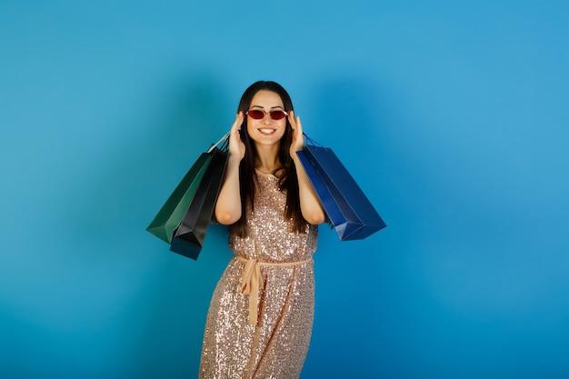 성공적인 쇼핑 후 많은 쇼핑 가방을 들고 빨간 안경 베이지 색 드레스에 젊은 아름 다운 아가씨.