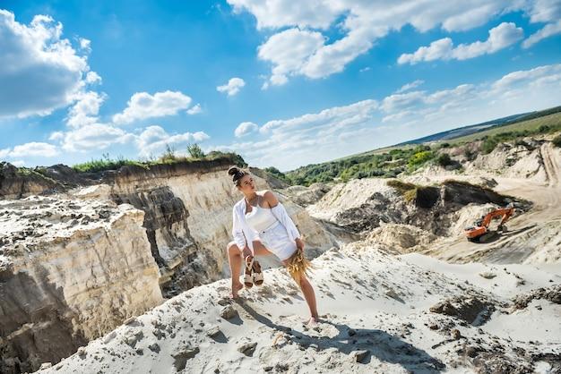 평상복을 입은 젊은 미녀는 모래 채석장, 휴가, 여름 여행에서 휴식을 취합니다