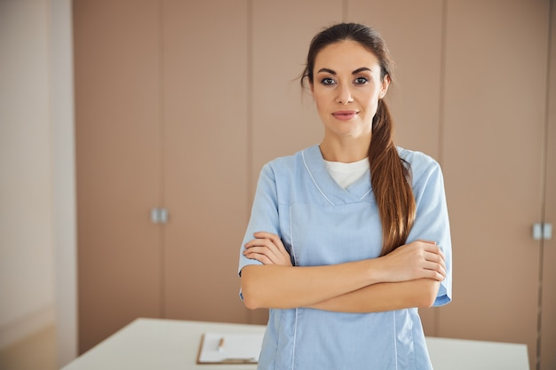 Young beautiful lady in medical uniform posing at office