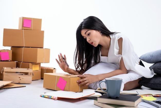 Молодая красивая дама упаковывает вещи и пишет на почтовом ящике, продает онлайн, работает из дома, с чувством счастья