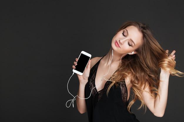 Giovane bella signora che mostra l'esposizione del telefono e la musica d'ascolto