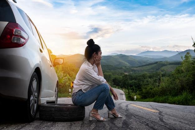 若い美しい女性が公道で助けを求めるために車の近くに座っています