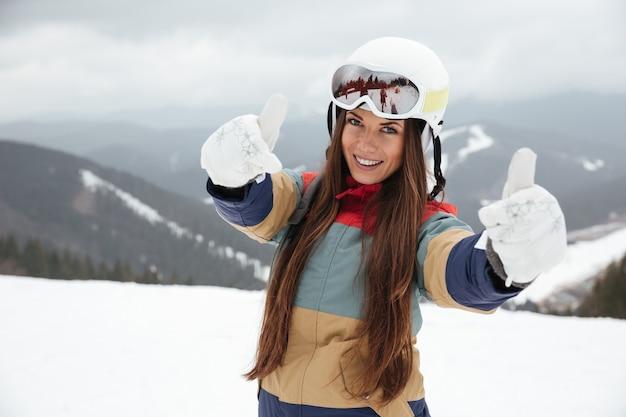 Молодая красивая сноубордистка на склонах морозным зимним днем делает большой палец вверх жест