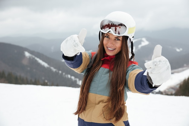 Young beautiful lady snowboarder on the slopes frosty winter day making thumbs up gesture