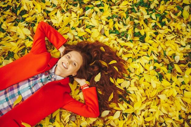 秋の紅葉に囲まれた若い美しい女性