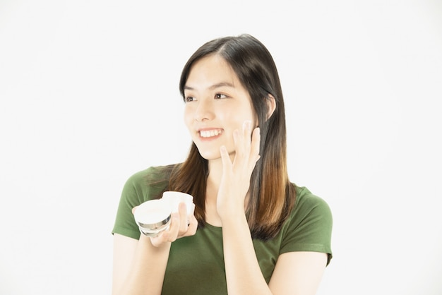 Young beautiful lady using moisturizer cream for face skin care - woman and cosmetic makeup face beauty skin care concept