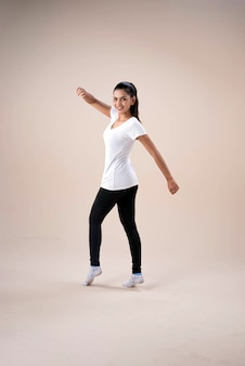 Young beautiful lady wearing sportwear,standing feet aparts kneel ,point toe down,raise hands up and downlittle twisted,dance workout for exercise,with happy feeling