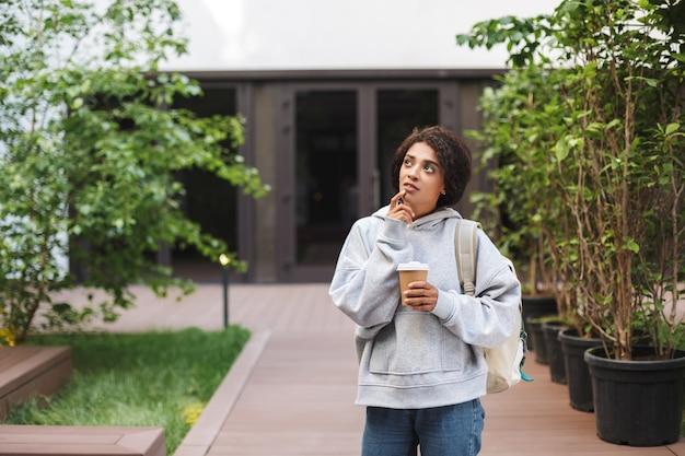 배낭과 커피 한잔으로 서있는 검은 곱슬 머리를 가진 젊은 아름다운 아가씨는 꿈꾸는 동안 손에 들고