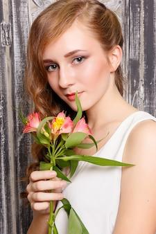 灰色の背景に花を持つ若い美しい女性。スキンケアのコンセプト。緑の花を手に、灰色の背景にスタジオで甘い少女の肖像画