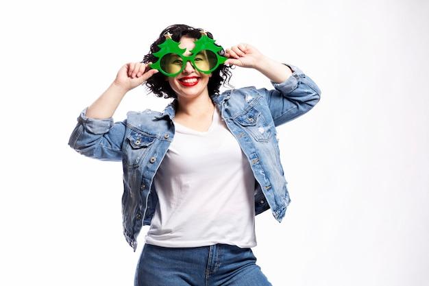 Молодая красивая смеющаяся брюнетка в джинсах и декоративных очках в виде елки. новогоднее настроение и веселье.
