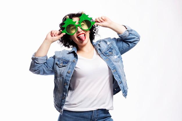 Молодая красивая смеющаяся брюнетка в джинсах и декоративных очках в виде елки.