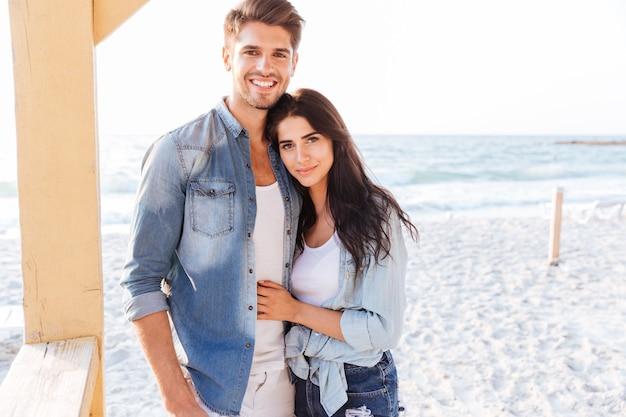 Молодая красивая смеющаяся пара, глядя друг на друга, стоя на пляже