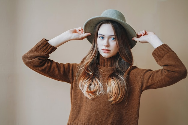 Young beautiful long brown-haired hair girl with blue eyes in felt hat and brown knitted sweater looking at camera on beige background