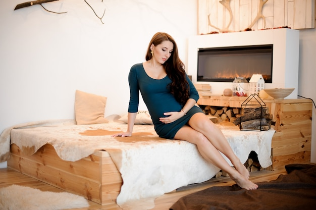 Young and beautiful long-haired pregnant woman sitting near the fireplace