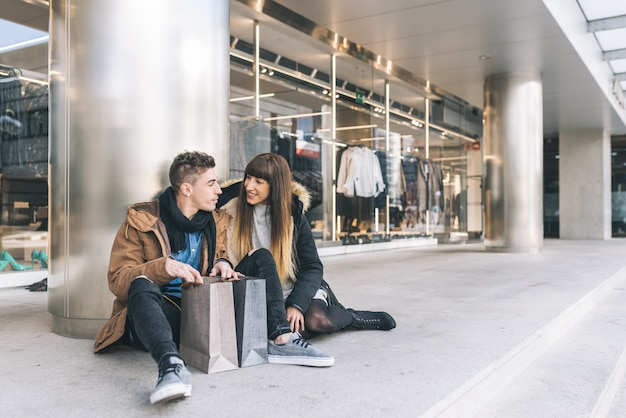 Young beautiful in love couple shopping around the street taking a break seating on the floor