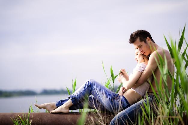 배경에서 녹색 자연과 여름 날에 강에 휴식을 갖는 젊은 아름 다운 사랑의 부부