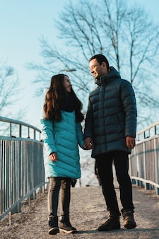 Young beautiful loving couple walking in city park near lake on valentines day.