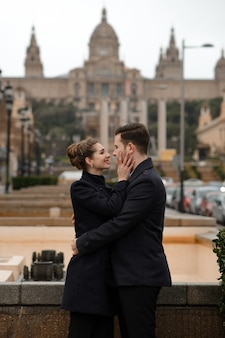 Young beautiful loving hispanic couple walks under an umbrella during the rain in plaza spain. couple posing against the backdrop of the national museum of art of catalonia.