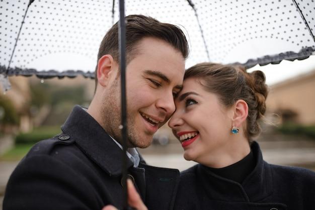 スペインのプラザで雨の中に傘の下で歩く美しい愛情のあるヒスパニックのカップル。カタルーニャ国立美術館を背景にポーズをとるカップル。