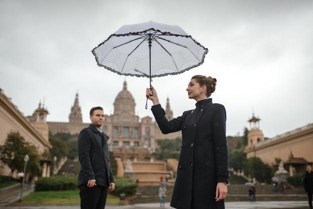 スペインのプラザで雨の中に美しい愛情のあるヒスパニックのカップルが傘の下を歩きます。カタルーニャ国立美術館を背景にポーズをとるカップル。