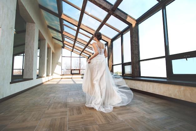 Молодая красивая роскошная счастливая невеста в модном свадебном платье в зале с большими окнами