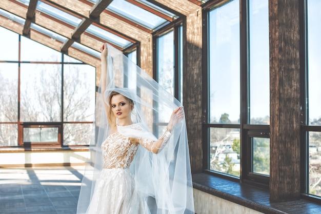 대형 창문이 있는 홀에서 세련된 웨딩 드레스를 입은 젊고 아름다운 고급스러운 행복한 신부
