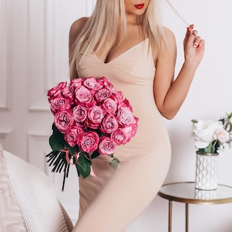 Young beautiful luxury blonde woman in beige elegant dress holding bouquet of pink roses