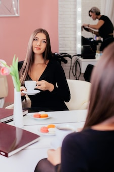 Young beautiful luxury brunette woman with cup of coffee