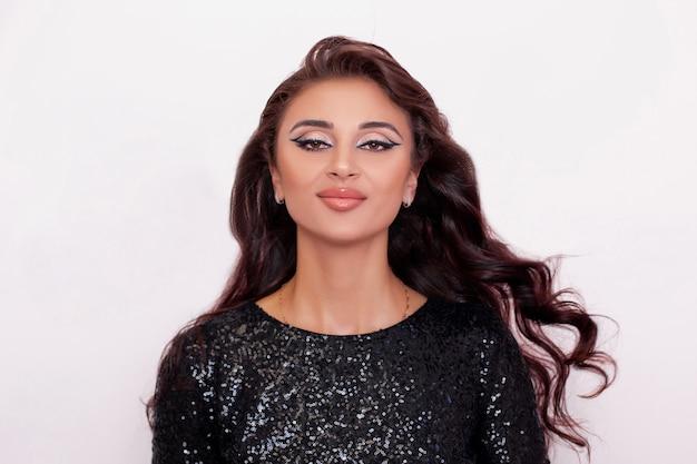 長い巻き毛の髪型とファッションメイクで若い美しい豪華なブルネットの女性