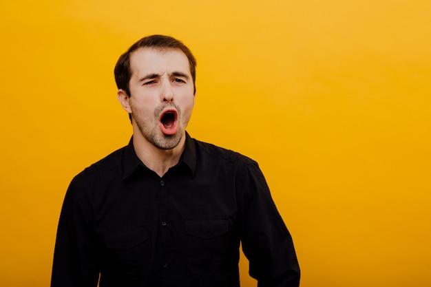 Young and beautiful man opens his mouth, screaming hard, standing on yellow background, copy space, positive emotions, isolated