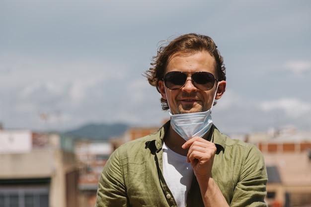 Молодой красивый человек снимает защитную медицинскую маску с лица