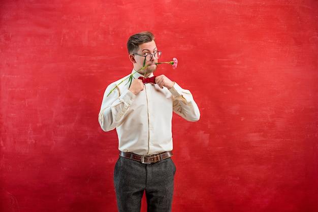 赤いスタジオに花を持つ若い美しい男