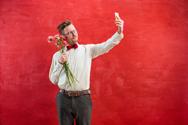 Young beautiful man with flowers and phone