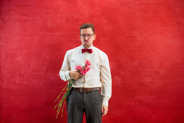 Giovane uomo bello con fiori in studio rosso
