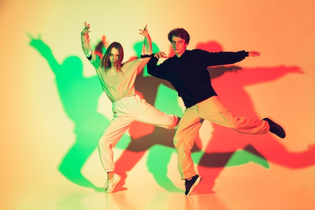 Young beautiful man and woman dancing hip-hop, street style isolated on studio