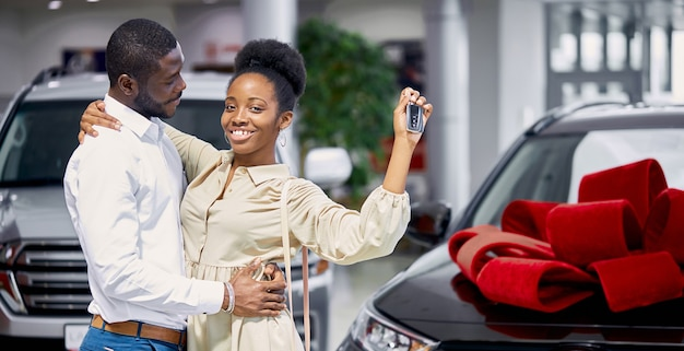 Young and beautiful married couple in cars showroom
