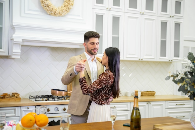 Young beautiful married couple in festive wear dancing in light stylish kitchen near table