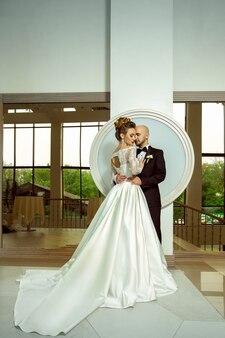 カメラに抱き締める結婚式のスーツの若い美しい夫婦