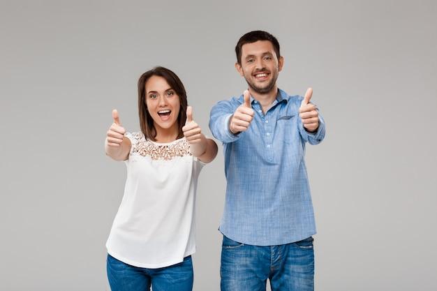 Young beautiful married couple posing, showing okay over grey wall
