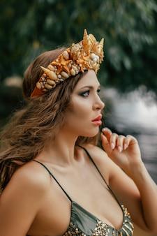 젊고 아름다운 인어 여자가 해수 코스프레 인어에 서 있습니다.