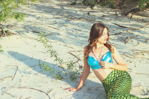 Young beautiful mermaid woman close up on the sea coast. cosplay mermaid.