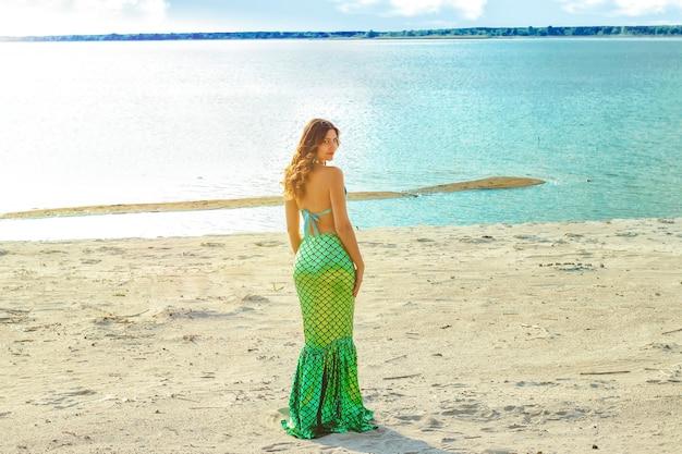 젊은 아름다운 인어 여자는 햇빛과 함께 바다 비용에 서 닫습니다. 코스프레 인어