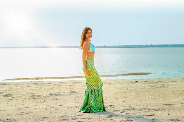 Young beautiful mermaid woman close up standing on the sea cost with sunlight. cosplay mermaid