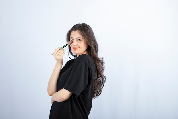 Young beautiful model applying shadow with brush on white wall.